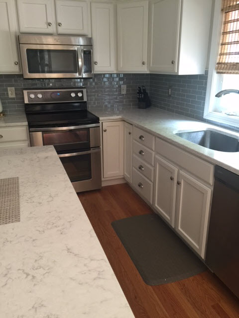 The completed kitchen renovation includes refinished cabinets.