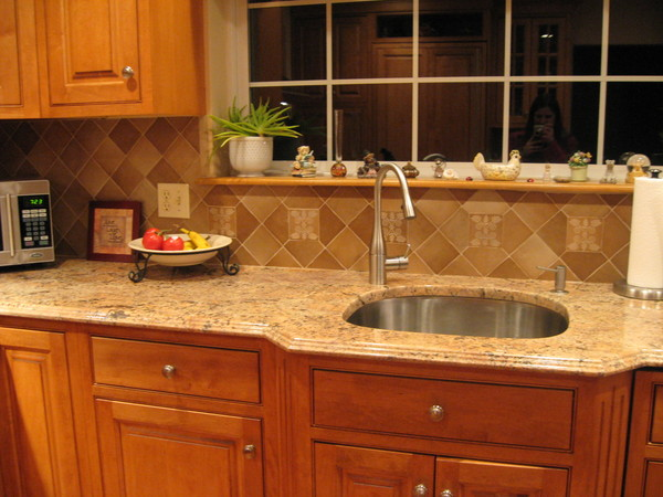 This kitchen backsplash features a related design element over the faucet area