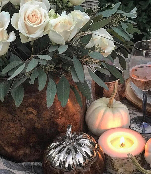 Consider using white roses as a live center piece to add glam to the table and visually transition from fall to winter